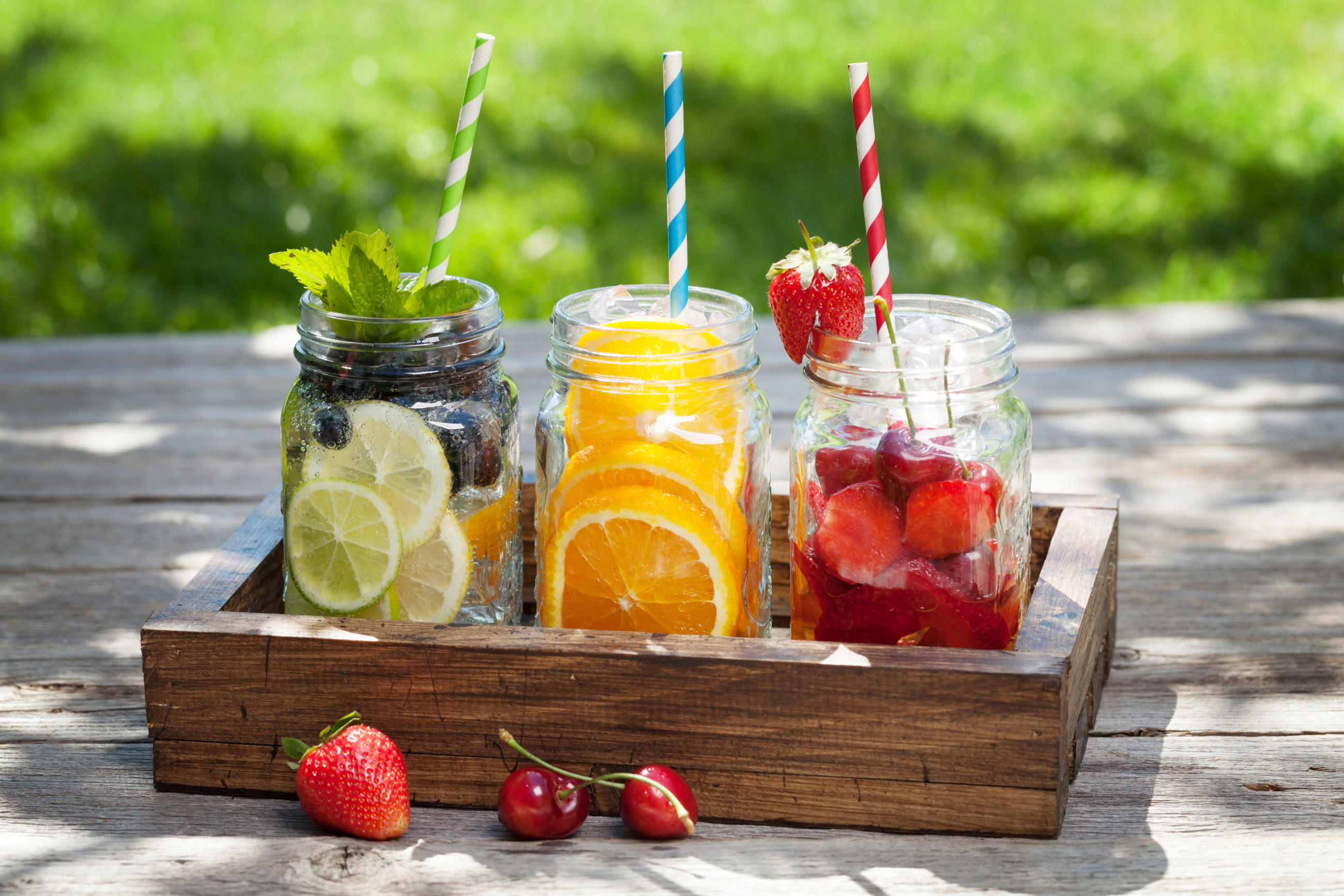 Three jars of fruit drinks with straws in a wooden box